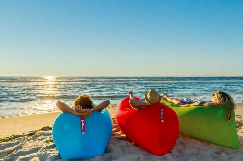 Groep vrienden op een Lamzac Fatboy op het strand tijdens zonsondergang