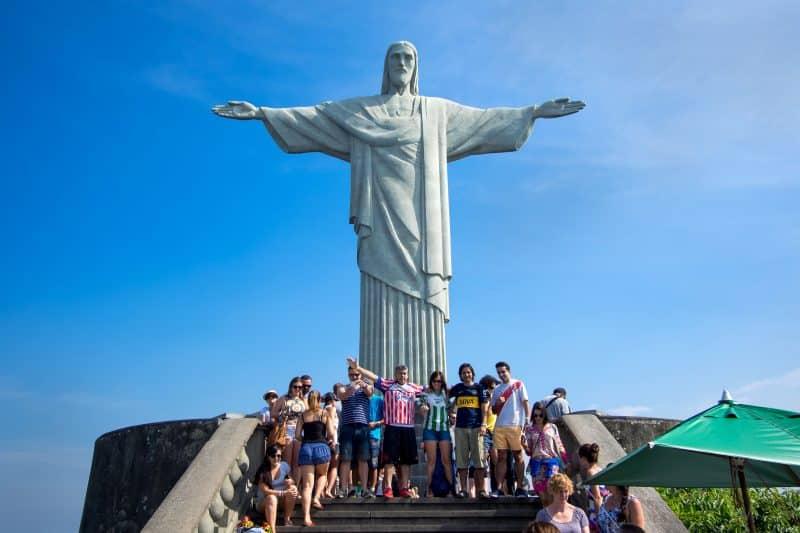 Poseren als Jezus voor het Christus standbeeld