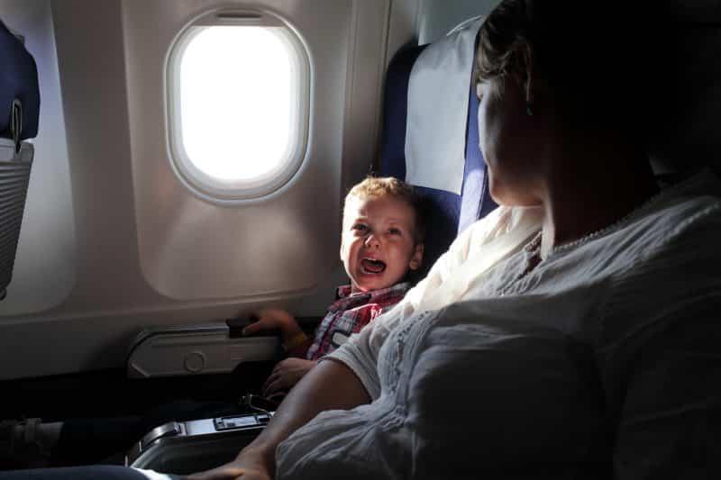 Huilend kind in een vliegtuig met moeder