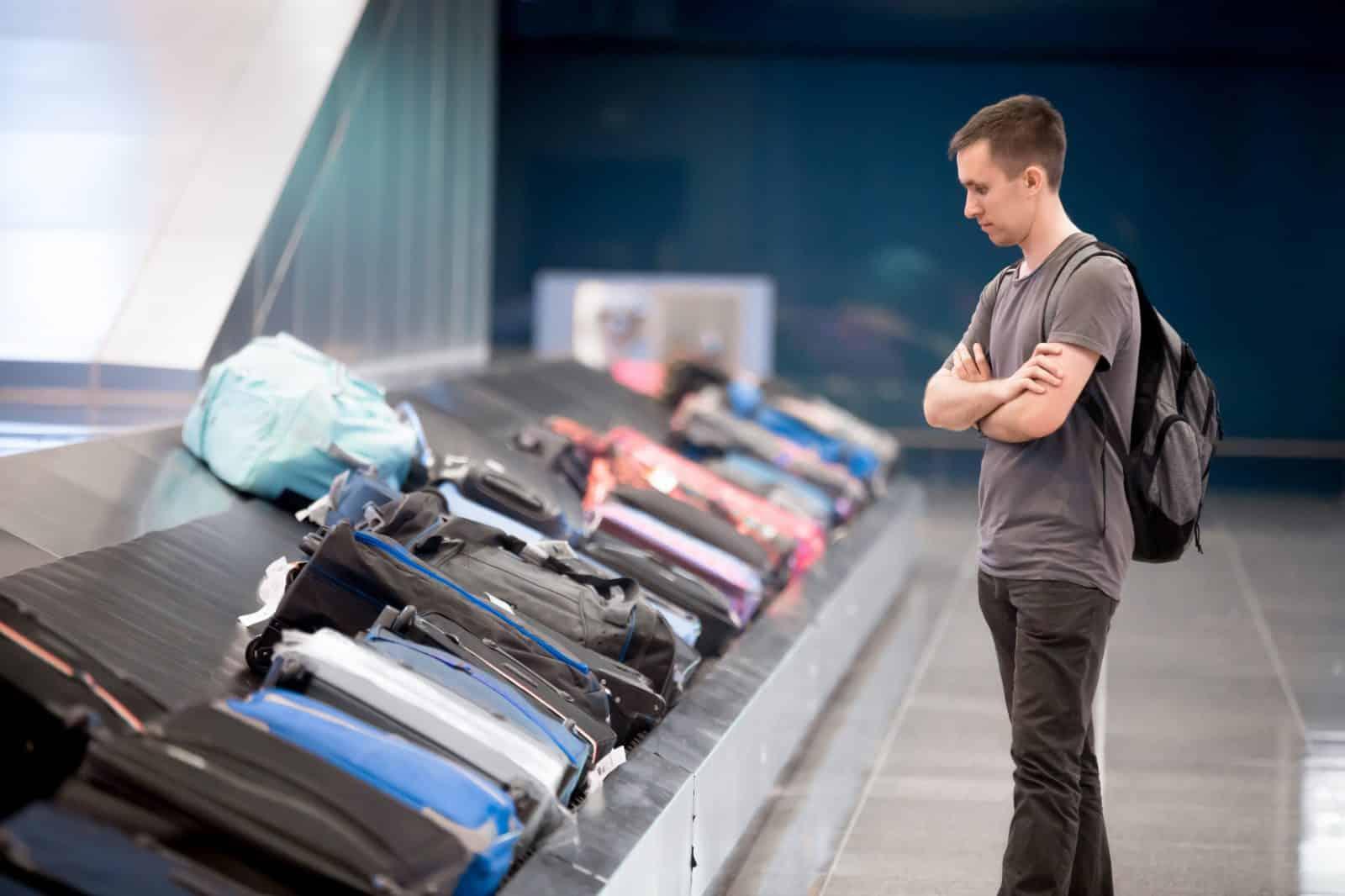 Jonge man wacht op zijn bagage op het vliegveld