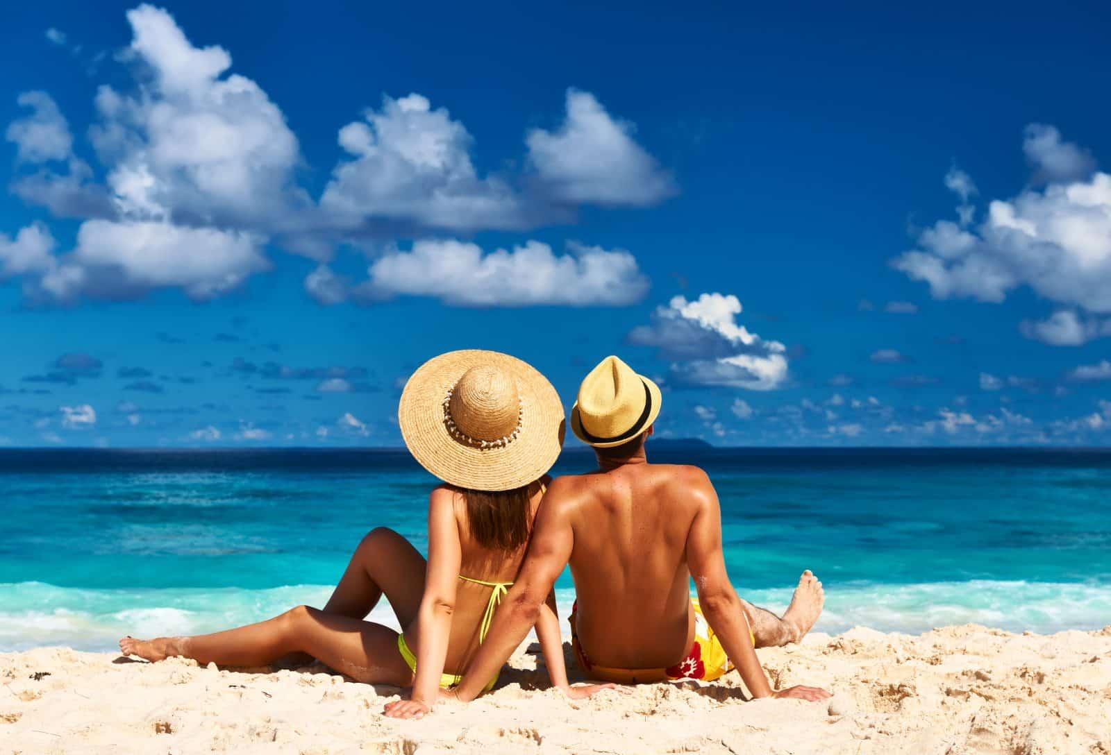 Stelletje op het strand met hoeden op