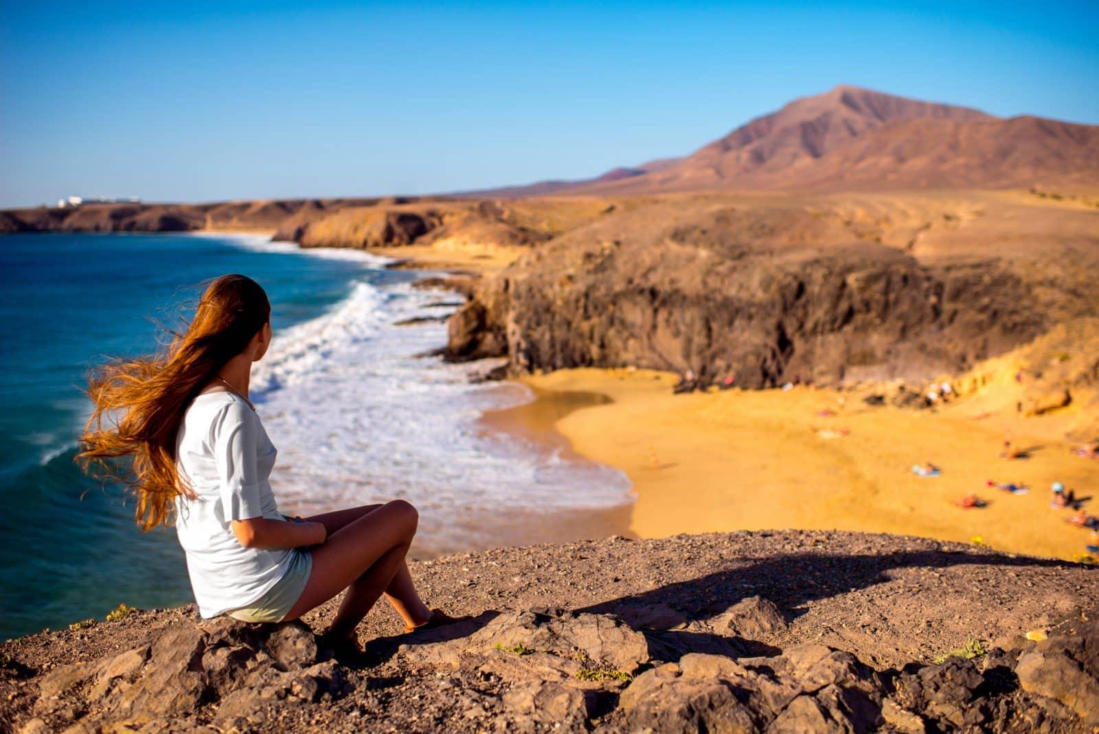 Vrouwelijke toerist kijkt uit over Papagayo beach op Lanzarote