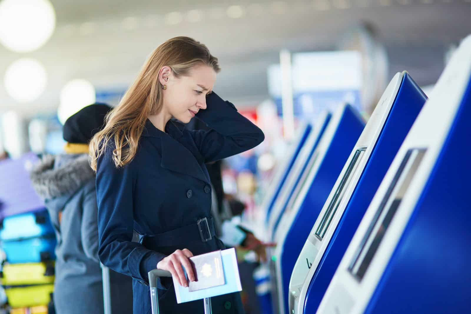 Jonge vrouw kijkt bedenkelijk bij een incheckbalie op het vliegveld