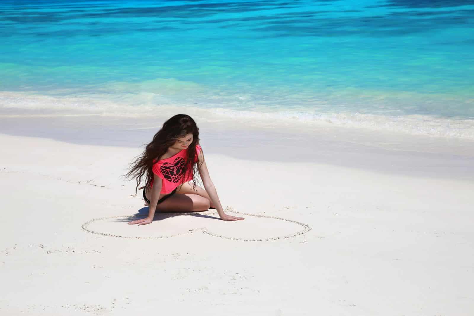 Vrouw op strand tekent hart in zand